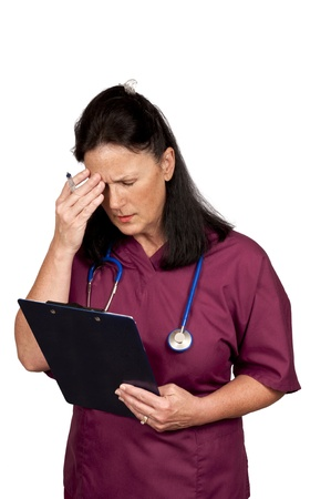 Mature female healthcare worker too tired to think   Wearing burgundy scrubs with blue stethoscope and isolated on a white background