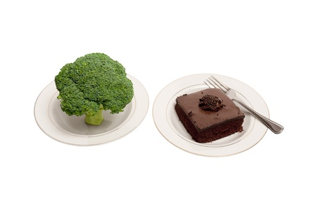 plates of food: A large stalk of broccoli and a piece of chocolate cake on white plates with a fork   Gives you a choice of healthy food or unhealthy food