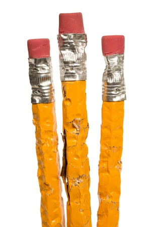 Group of chewed pencils standing upright on a white background.