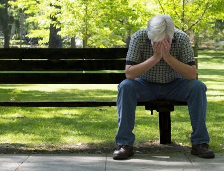 chateado: Homem deprimido sentado no banco