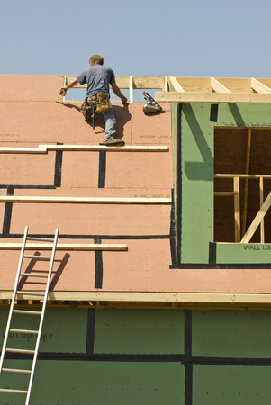 identifiable: Roofer Measures For Panel On New Construction ( Worker Is Not Identifiable)