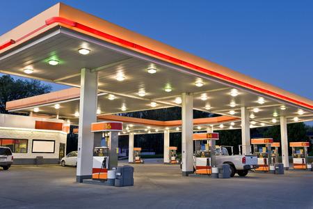fuelling station: Gasolinera y tienda de conveniencia al por menor tiempo de exposición  principios noche de la moderna estación de gasolina al por menor. Todos los logos y marcas que identifican se han eliminado, y el esquema de color original estación? S ha sido sustituido