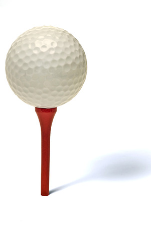 golf tee: Golf Ball On Red Golf Tee With Shadow