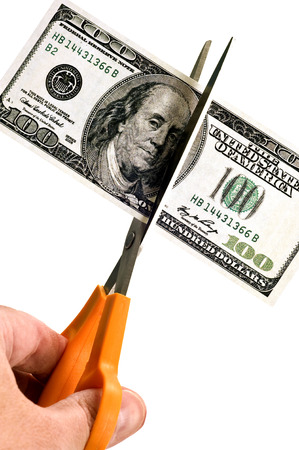 Budget Cutting With Hundred Dollar Bill On White Background Stock Photo