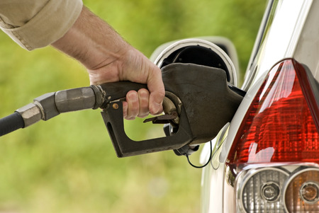 car gas: Hand Pumping Gasoline Into Gas Tank Stock Photo