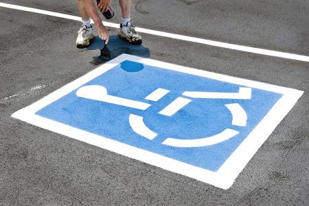 新しい障害者駐車場の看板を塗装