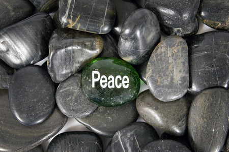 single word: Peace Word Hand Painted On Small Stone Surrounded By Other Stones