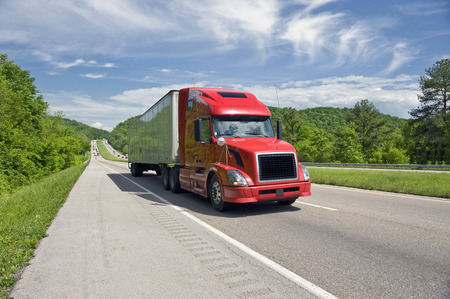Red Semi Truck On Interstate in Springtime Stock Photo