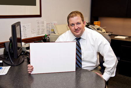 man holding sign: Cute Smiling Businessman Holding Sign Stock Photo