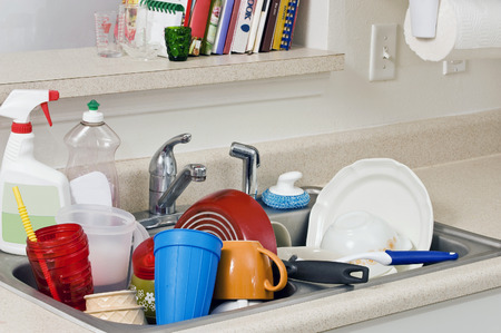 messy: Dirty Dishes Piled High In Kitchen Sink Stock Photo