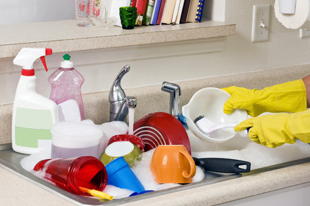 messy house: Hands Washing Dirty Dishes Stock Photo