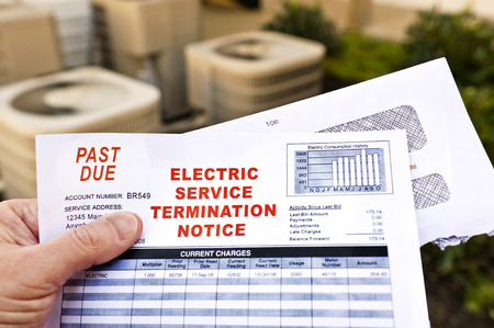 utility payments: Hand Holding Electric Service Termination Notice In Front Of Air Conditioning Units Stock Photo