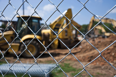 chain link fence: Construction Excavator Behind Chain Link Fence Stock Photo