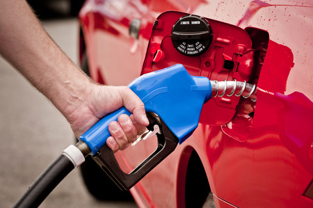 Hand Holding Blue Nozzle Pumping Gas Into Red Vehicle