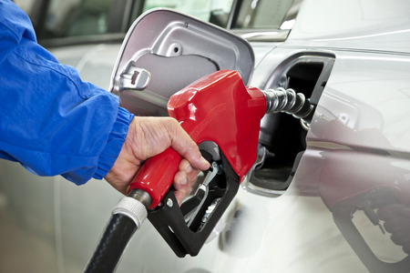 Man In Blue Jacket Pumping Gasoline From Red Nozzle