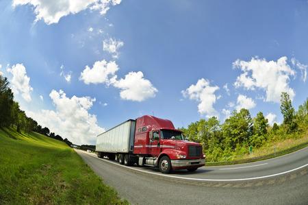 青い空の下の高速道路で大きなトラック
