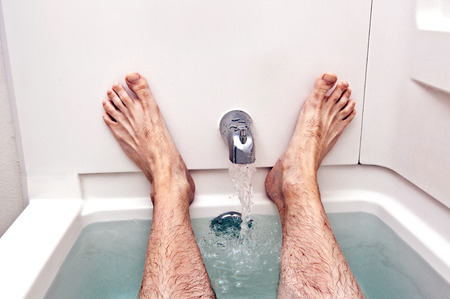 warm water: Man Resting In Tub Of Warm Water With Faucet Running