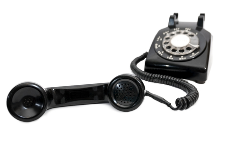 telephone receiver: Classic vintage rotary telephone with receiver in foreground and base in background out of focus