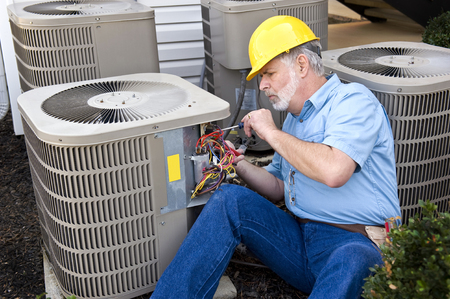 Repairman Working on Air Conditioning Unit