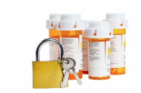 locking up: Keep Your Meds Safe Selective Focus On Gold Lock With Medicine Bottles Out Of Focus