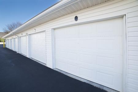 Rij van garagedeuren bij parkeerplaats voor flathuizen