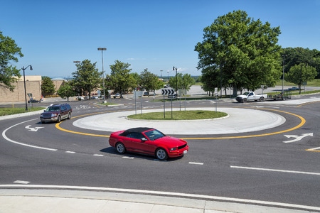 Traffic Roundabout With Vehicles In The Suburbs Stock Photo