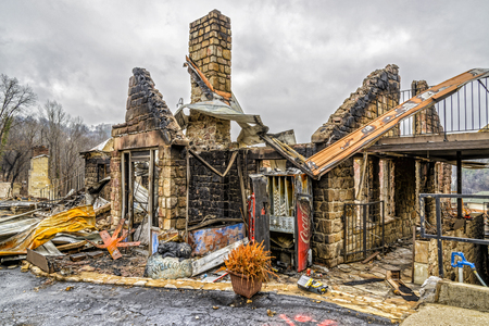 gutted: GATLINBURG, TENNESSEEUSA - DECEMBER 14, 2016: Only the shell of a motel office remains after being destroyed by a forest fire in Gatlinburg in late 2016.