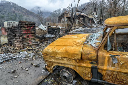 cremated: GATLINBURG, TENNESSEEUSA - DECEMBER 14, 2016: A cremated truck and a burned structure remain after a forest fire burned part of Gatlinburg in late 2016.