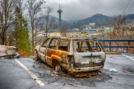 gutted: GATLINBURG, TENNESSEEUSA - DECEMBER 14, 2016: A gutted carcass is all that remains of a car in the aftermath of a forest fire that destroyed part of Gatlinburg, TN in late 2016.