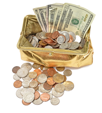 Vertical shot looking down at an open gold metallic coin purse filled with coins and fanned out five and twenty dollar bills on a white background. Stock Photo