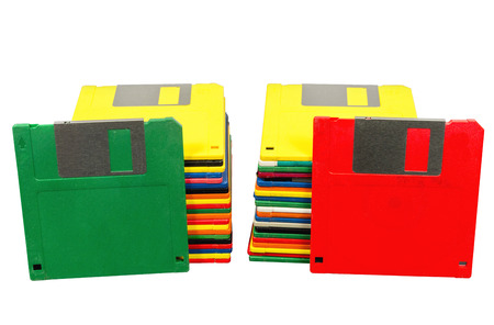 Horizontal shot of two stacks of old plastic multicolored disks.  A green disk is leaning against one stack and a red disk against the other.  Fronts showing.  White background. Reklamní fotografie