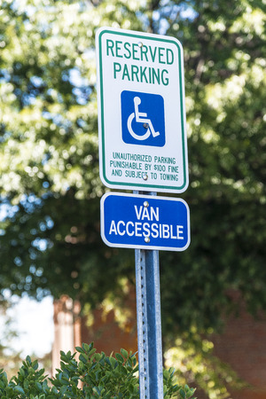 Vertical shot of a handicapped parking sign with a 15 mile per hour sign below it.  Out of focus trees and a building in the background.