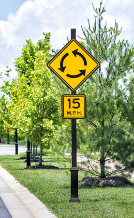 Vertical shot of a roundabout traffic sign with speed limit sign below in an upscale industrial park.  Green trees with sidewalk going past.  Cloudy sky. Stock Photo