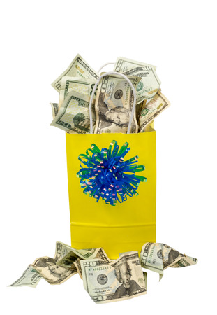 Yellow gift bag with blue bow on front overflowing with twenty dollar bills. Some have even landed in front of the bag.
