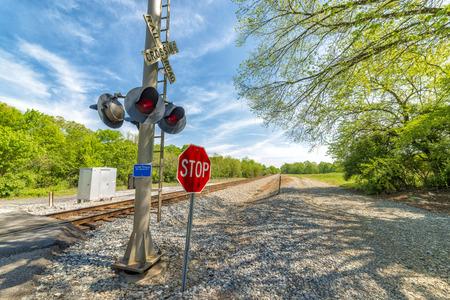 Horizontal shot of railroad crossing warning equipment and a stop sign.