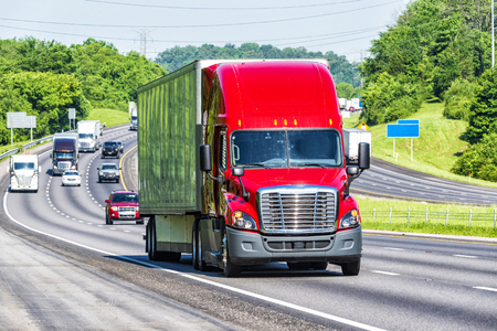 A red 18-wheeler leads other traffic down the interstate. Image shot on hot day. Heat waves from asphalt create distortion, especially on vehicles farther from camera, enhancing long telephoto effect.