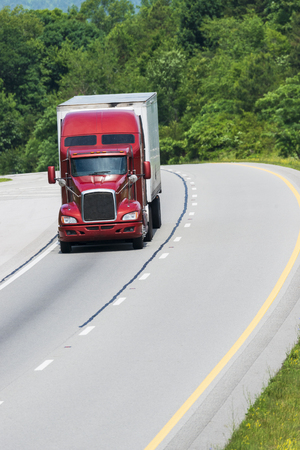 A single semi travels an interstate.  All logos have been removed from the vehicle.  The image is cropped loosely to provide a generous amount of copy space below, above and to the side of the truck.