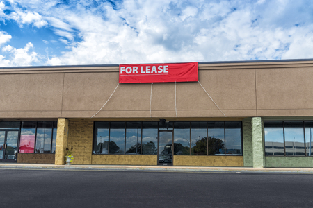 Sevierville, TN  United States - October 15, 2018: Horizontal shot of Retail Space Available in an old strip shopping center under a blue cloudy sky. Red For Lease sign hangs on the front.  EDITORIAL ONLY