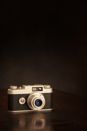 Vertical shot of an old 35mm camera on a brown background with copy space.  Partial reflection of camera on tabletop. Stock Photo