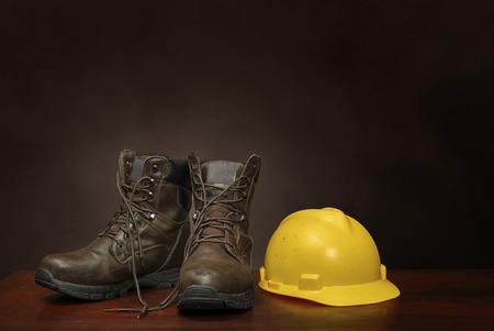 Horizontal shot of a pair of brown work boots and yellow construction helmet on a brown background with copy space. Foto de archivo