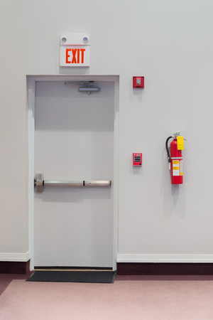 Vertical shot of an emergency exit door with a fire alarm, fire extinguisher, and an emergency light hanging on the wall next to it. Foto de archivo - 119829346