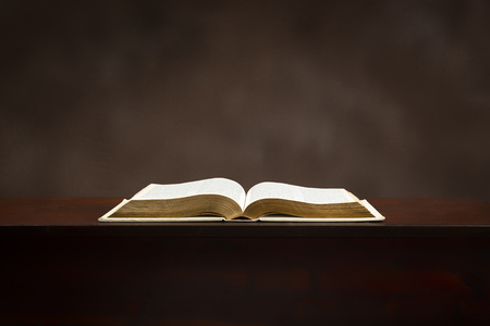 Horizontal shot of an old Bible lying open on a brown background. Imagens
