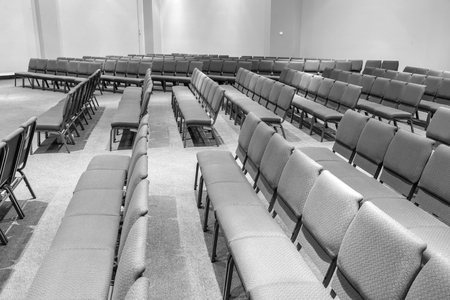 Horizontal black and white shot of empty auditorium seating standing at the side looking across.