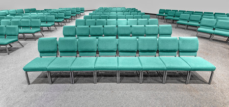 Horizontal shot of empty auditorium seating standing at the front looking toward the back of the auditorium. Stockfoto