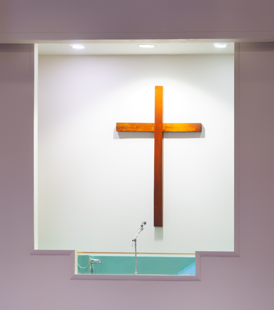 Vertical shot of a church baptistry with a wooden cross on the white wall behind it.