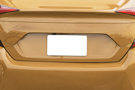 Horizontal shot of a blank white license plate on a gold car with copy space. Stock Photo
