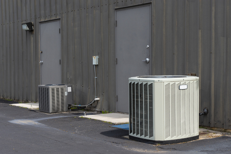 Horizontal shot of commercial air conditioners outside an aging office complex.