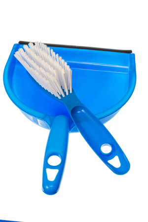 Vertical shot of a blue dustpan with a blue brush with white bristles laying on it. Isolated on white with copy space. Stockfoto