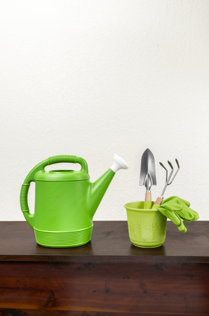 Vertical shot of a green watering can with a white spout next to a green pot with a trowel, gardening fork, and a pair of green gloves inside.  Wooden surface with white textured background.