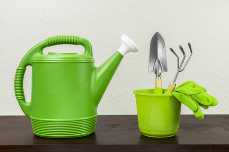 Horizontal shot of a green watering can with a white spout next to a green pot with a trowel, gardening fork, and a pair of green gloves inside.  Wooden surface next to a white textured background.